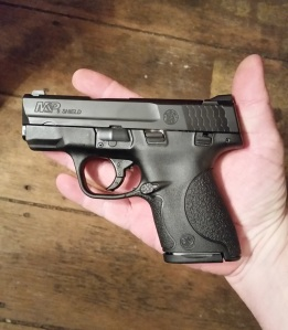 The 9mm S&W M&P Shield in the palm of the author's hand.  (7-round magazine inserted)